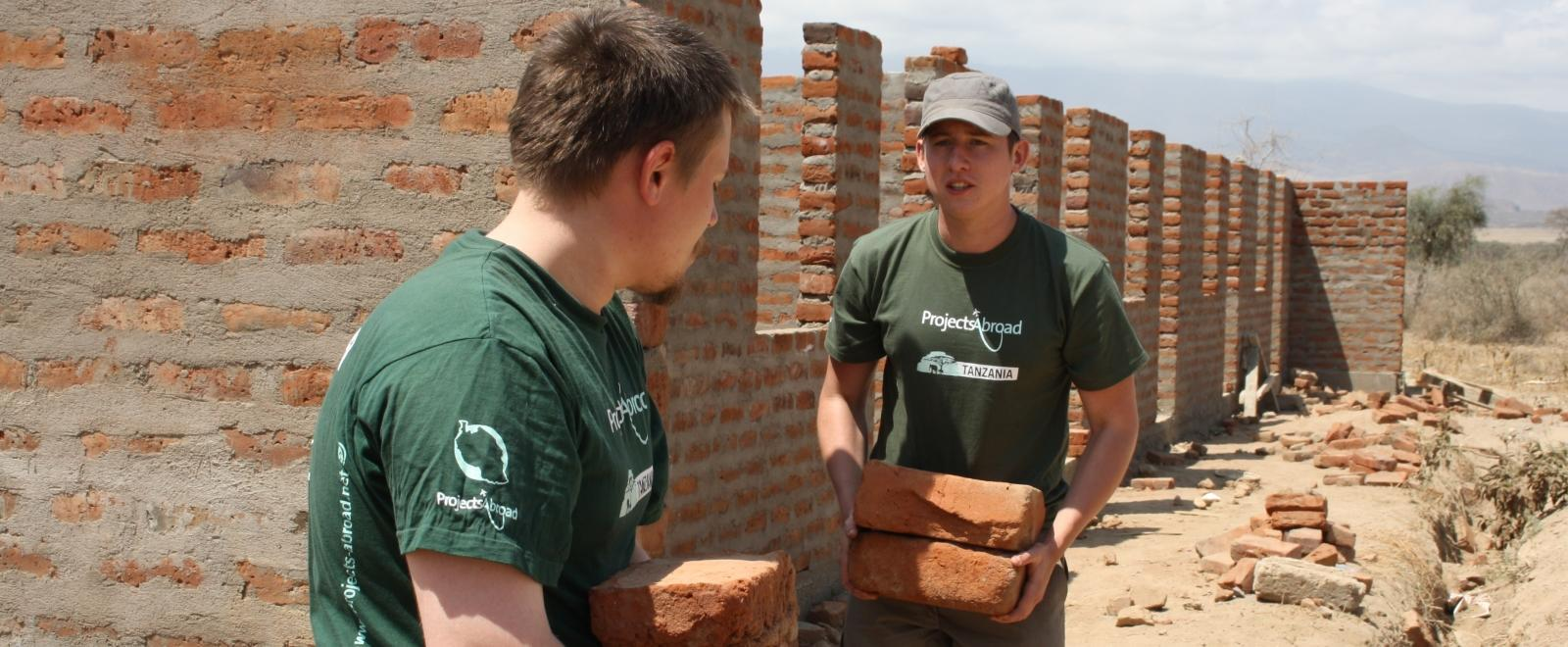 Teenage volunteers doing construction work in Tanzania carry bricks needed for a wall.